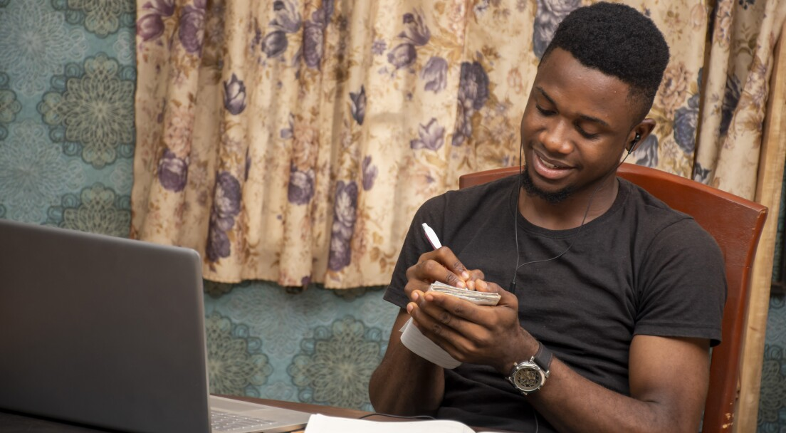 young african student receiving lectures online, taking notes