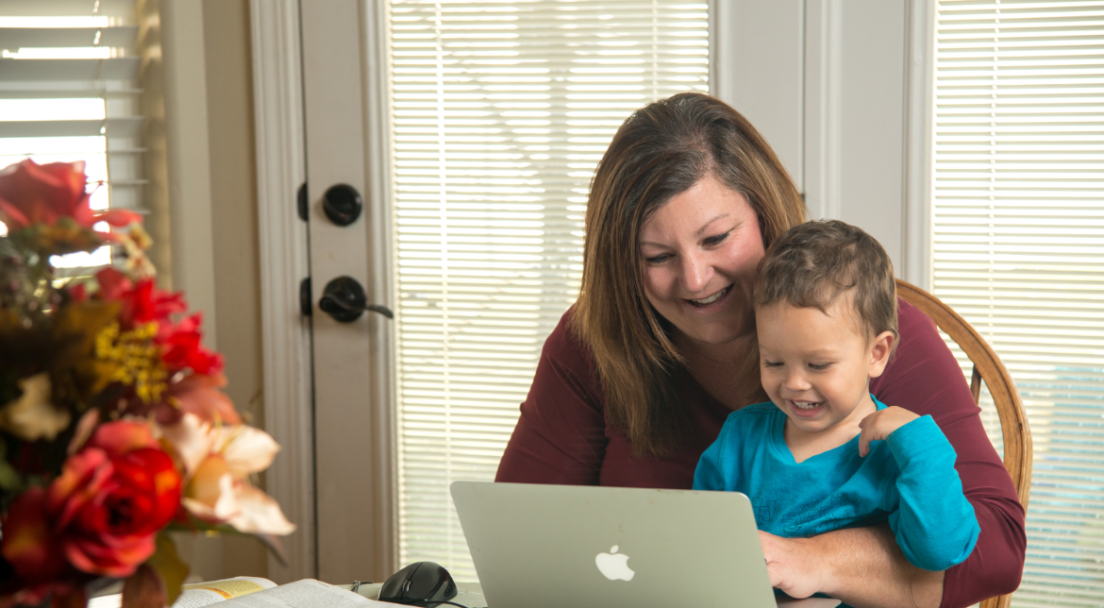Woman with small child sitting at table using Apple computer