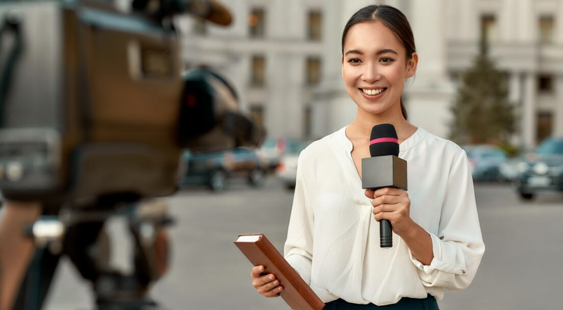 Portrait of professional female reporter at work. Young asian woman standing on the street with a microphone in hand and smiling at camera. Horizontal shot. Selective focus on woman.