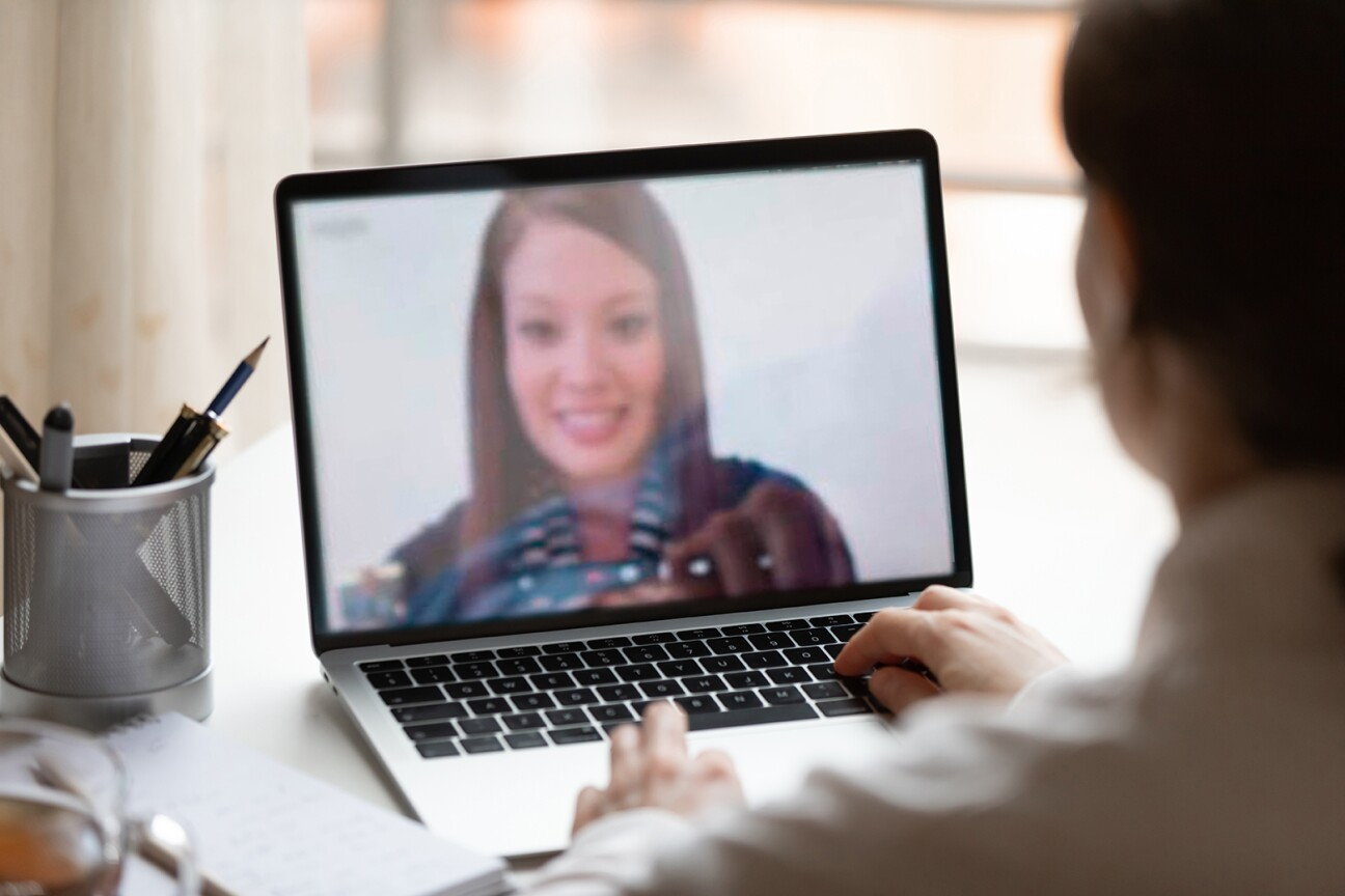Indian lady lead videocall, pc screen view over woman shoulder